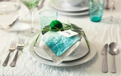 A blue dip-dyed napkin arranged on top of a bowl as part of a table setting.