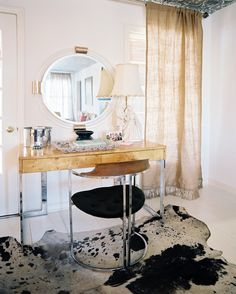 A hide rug in an office space with a round mirror and a wooden desk