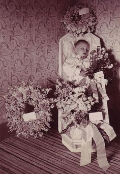 Vintage Photo of a Small Boy Post Mortem in His Coffin Surrounded By Flowers Wreaths