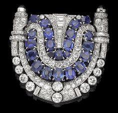 An art deco sapphire and diamond brooch, circa 1930 The openwork shield-shaped plaque of geometric design, composed of two rows of cushion-shaped and circular-cut sapphires, within a surround of baguette, old brilliant, rose, single-cut and trapezoid-shaped diamonds, highlighted with circular cabochon sapphire terminals, the gallery decorated with engraved greek key pattern