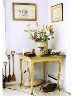 At Mellon's house in Massachusetts, country-style flowers, including goldenrod and cosmos, fill a stoneware vessel atop a painted table; positioned beneath the table are bird sculptures that reference the wildlife in the area.