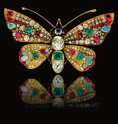 Antique Gemstone and Diamond Brooch, circa 1900. Designed as a Butterfly, the head and thorax set with a step-cut sapphire and emerald, and an oval and pear-shaped diamond, the wings set with variously shaped rubies, opals, emeralds and diamonds. #antique #brooch ♥≻★≺♥