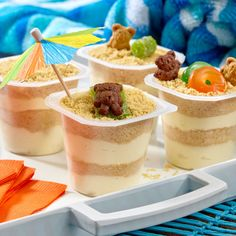 Summer Sand Pudding Cups: Dessert pudding cups layered with vanilla pudding mixed with cream cheese and crushed cookies then decorated to look like a summer beach scene