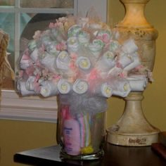 Baby bouquet shower gift. Fill the vase with travel size bath stuff then roll up onsies and socks for the flowers add tulle to take up space/make it fuller.
