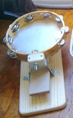This is a video demonstrating a DIY foot-drum I made for myself. The heart of it is an old tambourine. A used mounting bracket from a ceiling vent fan makes the A-frame stand. It's attached to an old board. The pedal is some mdf flooring offcuts I nailed together. I used a bit of trim from the kitchen to make a fulcrum. There is small bit of block attached to the top of the a-frame that I drilled a hole through for the eye-bolt and wingnut that attaches the tambourine. The trick is to wed...