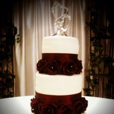 Wedding cake with burgundy roses and ribbon