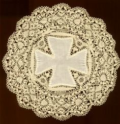 "The Maltese Cross ia a design Element that almost always identifies Maltese Lace. It was inserted into the lace when Maltese lace became so popular around Europe it was frequently copied.    It can be found woven into the lace or as shown here in the  fabric inset.   Another way to identify Maltesse lace  is the Cream colored silk used to make the lace or the very fat ""wheat-ear leaves"" shown below. Modern Maltese is now also made from cotton"