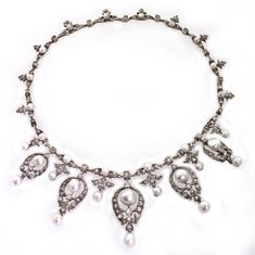 A late Victorian necklace comprising five graduated pearl and diamond drops of an openwork scrollwork cluster motif with natural pearl drops, diamond- and natural pearl-set floral motifs inbetween each drop, from a necklet chain of graduated pearl and diamond links with diamond drops, all of a foliate design, a diamond set within a square collet between each one, all diamonds estimated to weigh a total of 5.20 carats, all set in silver to a yellow gold mount, circa 1890