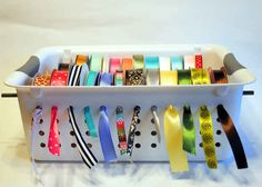 An insanely easy trick to turn a slotted tupperware bin into a ribbon organizer.