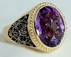 Men's custom 14K yellow gold Amethyst ring with black rhodium accented Fleur De Lis design sides.