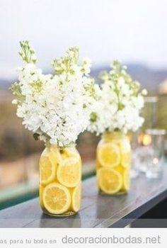 Centro mesa boda en verano con rodajas de limón y flores blancas
