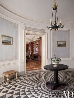Paved with a Roman-inspired mosaic, the elliptical entrance hall of a Naples, Italy, apartment designed by Studio Peregalli features 18th-century paintings by Pietro Antoniani as well as a Louis XVI stool; the French Empire chandelier is suspended above an antique English lavastone pedestal table.