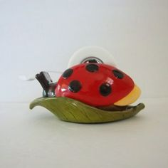 Vintage Ladybug Tape Dispenser featuring a cleaver ladybug design of a bug on a leaf with a soft covered bottom. It is weighted and heavy so it stays in one place when dispensing tape. Please not that the tape cutting blade is very sharp so be very careful and I do not recommend its use by children. There are a couple of chips to the paint on its back wings. This is a must have piece for your packaging and gift wrapping needs! A Colorful accessory for a teachers desk as well! It measures…