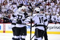 LA Kings teammates congratulate each other as they score another goal against Phoenix May 15, 2012. The Phoenix Fans decked out in white look on in dismay.