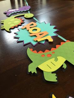 Roar! This banner is the perfect addition to your dinosaur party! The pictured banner measures approximately 30 inches in length with extra ribbon on each end for hanging. Each section measures approximately 6 inches in height. Made using high quality cardstock. Foam dots are used to add dimension. This item is made to order, so ribbon may vary from what is pictured (you will receive a similar ribbon of the same quality). Please message me if you are looking for a specific color…
