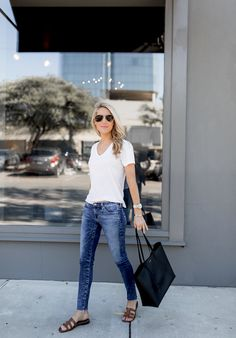 Pairing flat sandals with an effortless white tee and jeans is a casual look that still feels polished and put together...