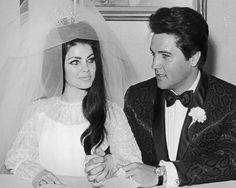 American rock n' roll singer and actor Elvis Presley (1935 - 1977) sits and holds hands with his bride Priscilla Presley on their wedding day in 1967. Photo: Hulton Archive, Getty Images