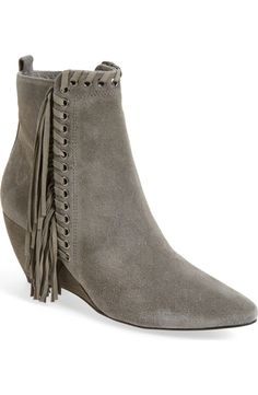 Whipstitched trim, grommet detailing and trailing fringe add a Western twist to this suede-crafted almond-toe boot set on a wrapped wedge heel.