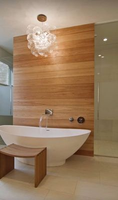 Frosted glass toilet door idea. Freestanding bath with warm wood look on wall behind