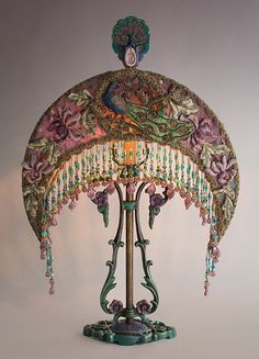 Beautiful antique art nouveau table lamp with flowers has a Peacock Moon crescent silk lampshade. The shade has rich bohemian antique textiles including stumpwork padded flower appliqués. A vintage traditional appliqué from India adorns the front. Exquisite embroidered net is on the side panels and when lit this shade has beautiful varigated tones. The shade has hand-beaded fringe in gold, blue, turquoise green and lavender. Perfect for world-traveler, bohemian or gypsy decor!