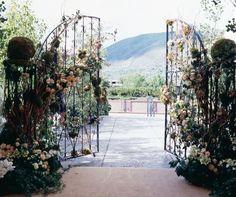 A Wrought-iron Gate Covered In Pale Roses And Vines Is Both Romantic And Rustic.