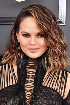 Let Chrissy Teigen be your lob inspo with this wavy textured cut and warm highlights.