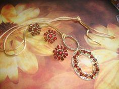 Conjunto formado por brincos, anel e cordão com pingente. Aplicação de strass vermelho escuro. Metal dourado.