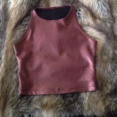 American Apparel crop top NWOT Metallic shiny maroon color. Fitted. 80% nylon. 20% elastane. Great for a night out with the girls. Sad to part with this but I have a feeling I won't be wearing it. The top is still listed at $35. I paid $45. NEVER WORN BEFORE. Available upon request. American Apparel Tops Crop Tops