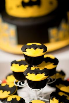 batman birthday cupcakes.   aka. my next birthday cupcakes.   just use icing that is thinker/harder.   roll out the icing and cut out yellow circles with a cookie cutter.   use a precision knife for batman symbols. by lorene