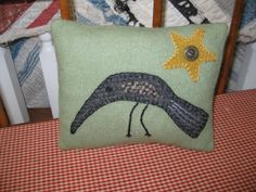 """small pillow with """"Hector"""" the crow."""