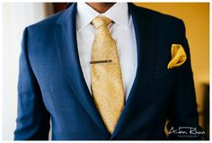 gold colored tie and navy suit