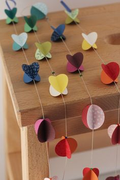 """Paper garland.  Use orange and black paint chips and a 2"""" round hole punch to make this garland.  It would look nice hanging from branches next to pictures or other decorations at a grad party."""