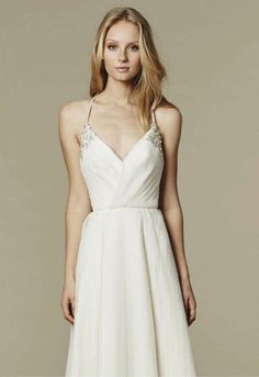 Ivory pleated net A-line gown with draped V-neck bodice, delicate straps and beaded appliqué, fullpleated skirt.