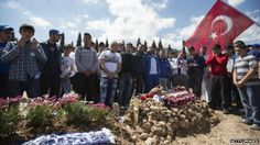 Turkey mine disaster: Three face charges over deaths: People pray in a Soma cemetery where several miners who died in the Soma mine explosion have been buried, in Soma, Turkey, 18 May 2014