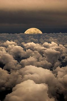 Moon emerging through the clouds in the sky. Photography by Victor Caroli