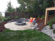 This fire pit patio is build into a hillside with the use of a rock wall.  People around the fire look out over a lake. Lakeside Cottages by Creative Landscape & Design.