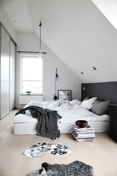 Black & white bedroom.  i like the idea of wall behind bed as different color... wouldnt you knock your head on the angled wall though?