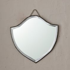 "Create a gallery wall or add depth to any space with this bevel-edged mirror in the shape of a shield.- Galvanized iron, glass- Wipe clean with damp cloth and glass cleaner- Hanging chain included- Imported9""W, 9.25""L, 0.25""D"
