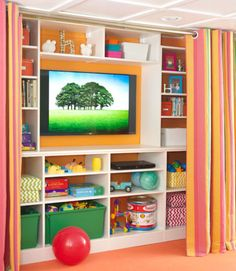 Selke transformed a recessed area into a media center with custom shelving. Toys that once were scattered everywhere are now housed in durable plastic bins stored where the twins can grab them, while breakable items (the TV, framed photos) are placed out of their reach. The striped panel curtains slide shut in a jiffy to conceal it all. Mike, a true seat-of-his-pants handyman, figured out how to create the suspended ceiling by watching YouTube videos. Benjamin Moore paint in Fruity Cocktail…