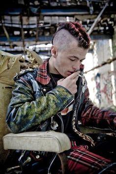 Male punk with a bihawk, leather jacket, red plaid pants