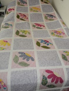 Isabelle's quilt: appliqued flowers on pink background, alternating blocks are hand quilted heart within a heart.