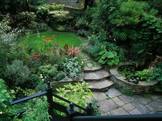 A natural screen of foliage plants, flowering plants and small trees make for a private, traditional garden oasis.