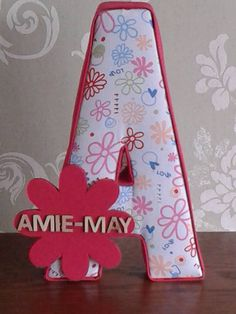 https://www.facebook.com/alphabet.craft  Handmade fabric A - Covered in flowers, hearts & love - Pink, edged in cerise, with a cerise wooden flower.  Fabric letters stand at aprox 20cm tall and are covered front and back with fabric, with light padding to the front.  This lovely letter would make an ideal gift for any special occasion e.g. Birthday, Christmas or Christening.  These letters look great standing of even as wall art on any nursery / playroom.
