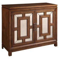 """Showcasing mirrored front doors with geometric overlay, this refined chest is perfect for stowing extra table linens in the dining room or towels in your master bath.   Product: ChestConstruction Material: Wood, pewter, metal and mirrored glassColor: TobaccoFeatures:  Two doorsInterior adjustable shelvingPewter hardware Geometric overlayDimensions: 38"""" H x 42"""" W x 16"""" D"""