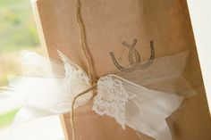 Fancy gift bags for hotel guests, dressed up with lace and tulle and a custom stamp, filled with the couple's favorite candies and custom-brewed beer created by the bride's family.