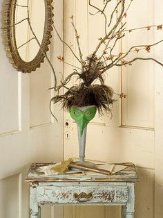 Transform a tall vase into a witch head by filling the vase with branches and feathers, tying them at the top to create the illusion of a pointy hat. Adorn the vase with a green mask for the face. Place the wicked decoration in the front hall to greet your guests with a cackle.
