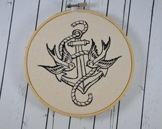 Beautifully stitched on a natural shade of canvas this vintage tattoo style hoop art is framed in a wooden bamboo hoop. Featuring a pair of swallows overlaying an anchor. This hoop measures in dia Vintage Style Tattoos, Retro Tattoos, Anchor Wall Art, Navy Tattoos, Sparrow Tattoo, Retro Fan, Symbolic Tattoos, Modern Embroidery, Popular Tattoos