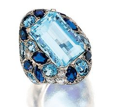 AQUAMARINE, SAPPHIRE AND DIAMOND RING, SUZANNE BELPERRON, 1950S Of oblong form, set at the centre with a step-cut aquamarine bordered by oval and circular-cut similar stones, marquise-shaped sapphires, circular-, single- and brilliant-cut diamonds, mounted in platinum - Photo c/o Sotheby's