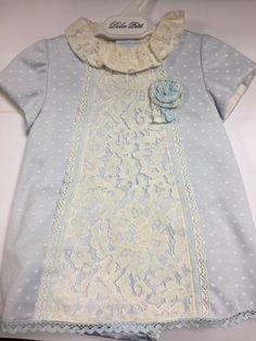 Dolce Petit Baby Girls Pale Blue Dress With All-Over Cream Polka Dots And A Cream Lace Overlay Down The Front With A Flower Detail. The Dress Has A Lace Collar Spanish Baby Clothes, Pale Blue Dresses, Lace Collar, Lace Overlay, Baby Girls, Polka Dots, Short Sleeve Dresses, Cream, Detail