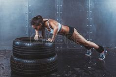woman strength: Sportswoman. Fit sporty woman doing push ups on tire strength power training concept crossfit fitness workout sport and lifestyle